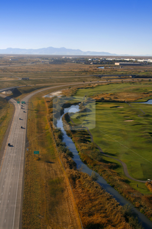 Overlooking at a Golf Course and a Pond along the Highway stock photo, Aerial Shot of a Golf Course along the highway by Mehmet Dilsiz