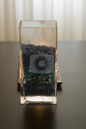 Vase behind a candle stock photo, Vase full of pebbles behind a candle by Mehmet Dilsiz