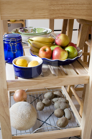 Kitchen Island with fruits, lemon, potatos, onion on the shelf stock photo, Kitchen island with apples, bananas, lemon, cantelope, onion, jar and bowls by Mehmet Dilsiz