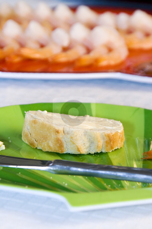 Close up on sliced bread on a table stock photo, Close up on a sliced bread with blurred shrimps on the background by Mehmet Dilsiz