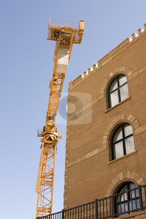 Construction Crane next to a Building stock photo, Construction Site Crane by Mehmet Dilsiz