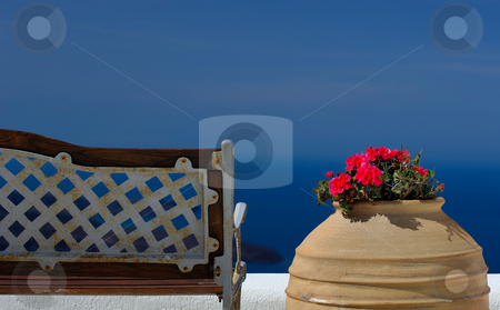 Serenity stock photo, Image shows a bench and a pot with flowers on the island of Santorini overlooking the magnificent view by Andreas Karelias
