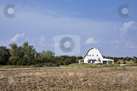 Barn House stock photo, Farmhouse sits on a green lawn beyond a field of stubble in rural Kansas by Bart Everett