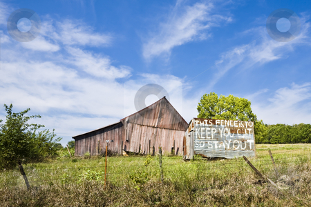 Dilapidated Barn Warning stock photo, A dilipidated barn sits behind a fence and a hand-painted warning sign in Kansas by Bart Everett