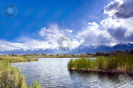 Sierra Storm on a Pond stock photo, Cumulus clouds roll over mountains toward a pond in California's Eastern Sierra by Bart Everett