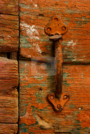 Door handle stock photo, Image shows a rusty handle on a highly textured country door by Andreas Karelias