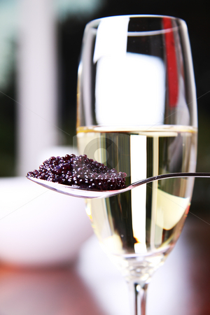 Caviar and champagne stock photo, Black caviar on a spoon next to a glass of champagne by Daniel Kafer