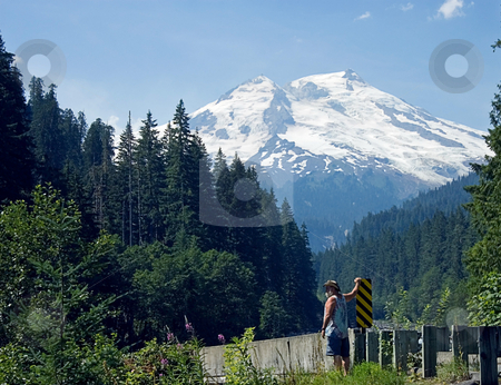 Man at Bottom of Beautiful Snow Capped Mountain stock photo, This man is standing at the base of beautiful Mt. Baker in Washington State, an awesome snow capped volcanic mountain, complete with forest in the foreground. by Valerie Garner