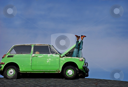 Humorous Mannequin Legs Sticking Out of Car stock photo, This humorous photo depicts a woman's mannequin legs sticking out of the hood of a small green car's hood against bright blue sky. by Valerie Garner