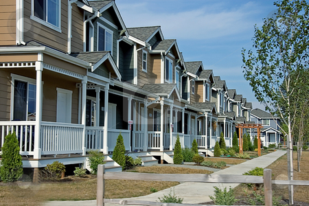 Row of Newer Townhouses stock photo, This is a newer neighborhood with a row of beautiful townhouses against a bright blue sky. by Valerie Garner