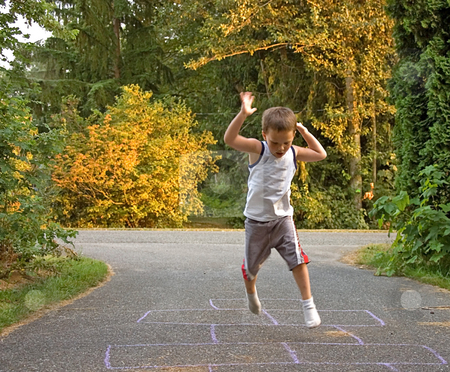 Little Boy in Mid Air Playing Hopscotch stock photo, This little boy is caught in a jump mid air as he's playing hopscotch outdoors. by Valerie Garner