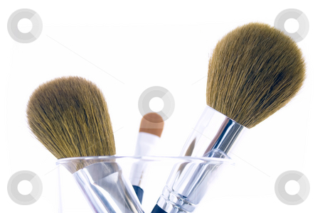Set of three makeup brushes stock photo, Set of three makeup brushes for face powder, concealer and eye shadow, in a glass. Isolated on white background. by Natalia Banegas