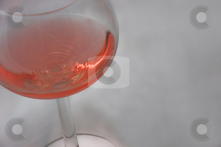 Glass of Pink Wine stock photo, This is a single glass of pink wine in a clear wine glass on a textured light background. by Valerie Garner