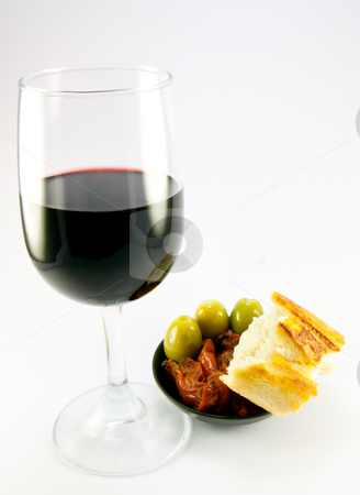 Sun Dried Tomatoes and Red Wine stock photo, Pile of red sun dried tomatoes with three green olives and crusty bread in a small black dish with a glass of red wine on a plain background by Keith Wilson