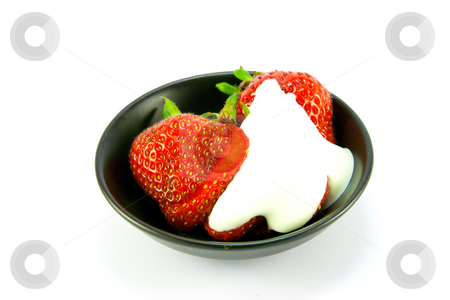 Strawberries and Cream stock photo, Sliced and whole red fresh strawberries with cream in a small black dish on a white background by Keith Wilson