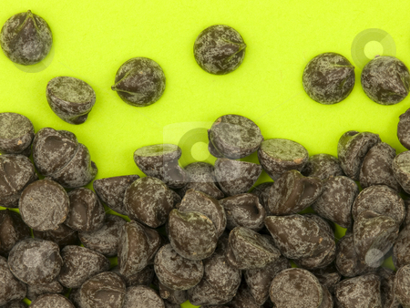 Chocolate Chips stock photo, Chocolate chips on a bright green background by John Teeter