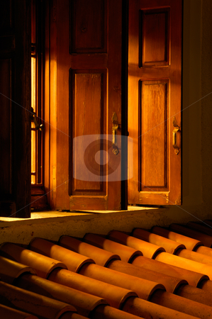 Let there be light stock photo, Picture shows an open window allowing golden light to illuminate the roof outside by Andreas Karelias