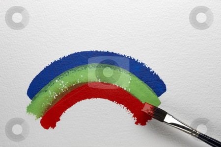 RGB rainbow stock photo, Artist's brush paints red, green and blue rainbow on textured watercolor paper by James Barber