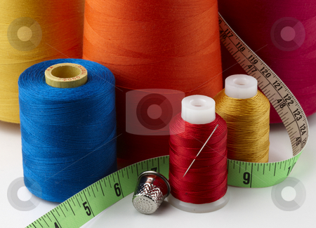 Spools of thread stock photo, Colorful spools of thread with tape measure, needle and thimble by James Barber