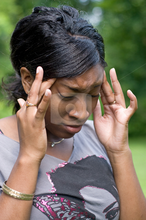 Painful Headache stock photo, This young woman is experiencing intense stress or pain from a splitting headache. by Todd Arena