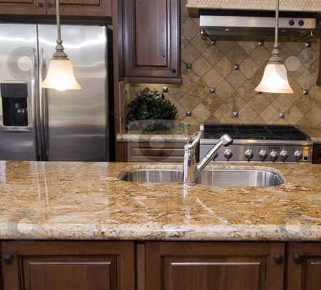 Luxury kitchen detail stock photo, Modern luxury kitchen focusing on island granite counter top and sink by Paul Hill