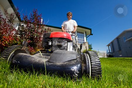 Mowing the lawn stock photo, A man mowing the front lawn with focus on the front by Steve Mcsweeny