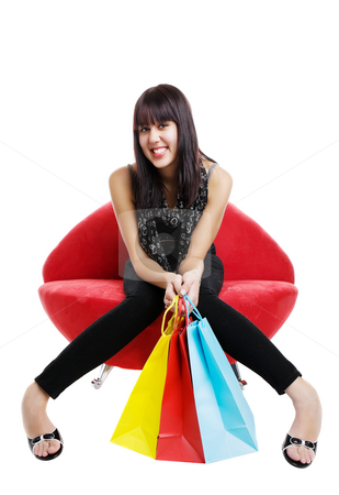 Resting shopper stock photo, Happy mixed race shopper resting on a lip chair by Steve Mcsweeny