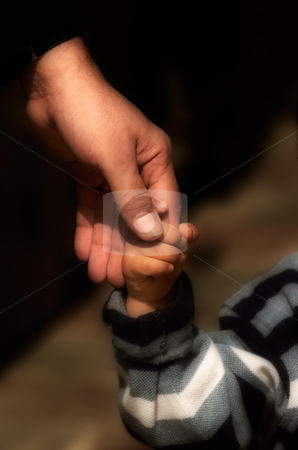Growing up stock photo, Image shows a hand of an adult holding the hand of a small child by Andreas Karelias