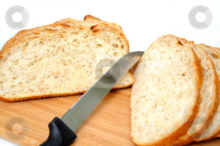 Sliced Cracked Wheat Sourdough Bread stock photo, Slices of fresh sourdough bread with a serrated knife and cutting board on a white background. by Lynn Bendickson