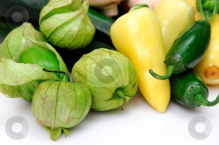 Tomatillo And Chili Peppers stock photo, Yellow and green chili peppers with fresh tomatillos, ingredients for salsa on a white background. by Lynn Bendickson