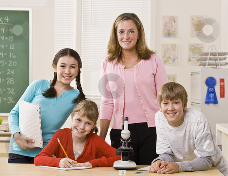 Teacher, students and microscope in classroom stock photo, Teacher, students and microscope in classroom by Jonathan Ross