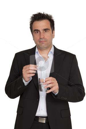 Young businessman take pills stock photo, Young businessman keeps in his hands one bubble pill and a glass of water by Marios Karampalis