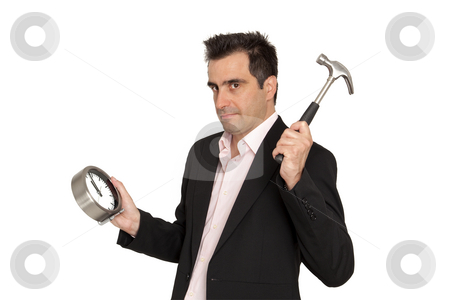 Young businessman breaks the clock of his work with a hammer stock photo, Young businessman nervous, he tries to breaks the clock of his work and making grimaces by Marios Karampalis