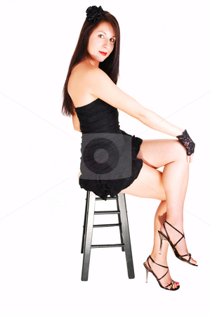 Lady in black dress. stock photo, Young pretty woman sitting on a bar chair  in an black dress and gloves, for white background. by Horst Petzold