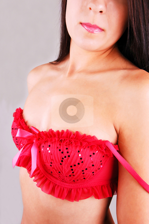 Young woman in red bra. stock photo, Young pretty woman with an very nice red bra, the shoulder strap are down, for light gray background. by Horst Petzold