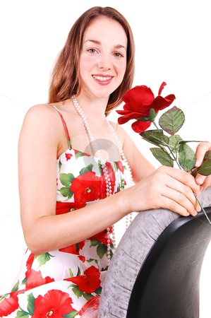 Pretty girl in dress with rose. stock photo, Pretty young woman sitting on a office chair backwards in a nice colorful dress and holding an red rose in her hand. For white background. by Horst Petzold