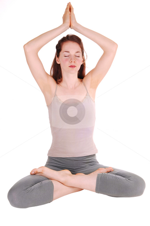 Young woman doing yoga. stock photo, Pretty slim girl in workout outfit sitting on the floor, her hands over the  head and the legs grossed meditating with yoga. On white background. by Horst Petzold