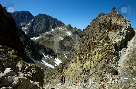 Hiker on steep path stock photo, Hiker on a steep path in sharp stone mountains in sunny day by Juraj Kovacik