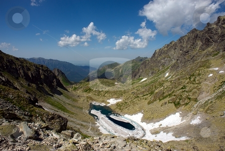 Melting frozen mountain lake stock photo, Melting frozen mountain lake in stone valley by Juraj Kovacik