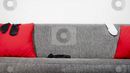 Sofa and socks stock photo, Socks in a sofa with pillows by Fredrik Elfdahl