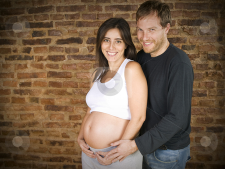 Waiting for the first one stock photo, Pregnant young couple smiling at the camera. by Ignacio Gonzalez Prado
