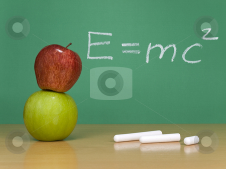 Theory of relativity stock photo, Einsteins formula of theory of relativity on a chalkboard. Some chalks and apples on the foreground. by Ignacio Gonzalez Prado