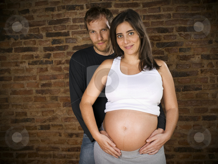 Waiting for the first one stock photo, Young couple holding the belly of the pregnant woman. by Ignacio Gonzalez Prado
