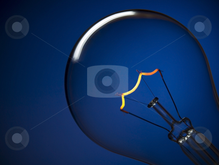 Bulb light over blue stock photo, Close up on a turned on light bulb over a blue background. by Ignacio Gonzalez Prado
