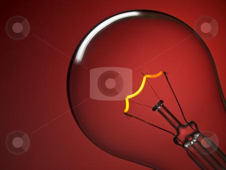 Bulb light over red stock photo, Close up on a transparent light bulb over a red background. by Ignacio Gonzalez Prado