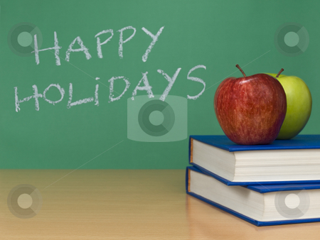 Happy holidays stock photo, Happy holidays written on a chalkboard. Two apples over books on the foreground. by Ignacio Gonzalez Prado