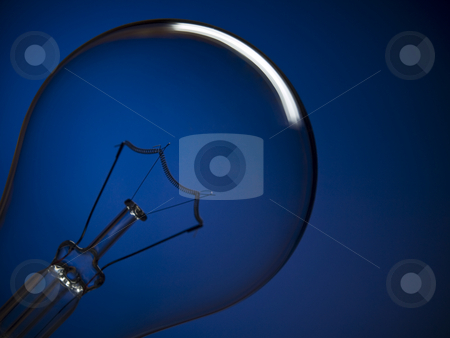 Bulb light over blue stock photo, Close up on a transparent light bulb over a blue background. by Ignacio Gonzalez Prado
