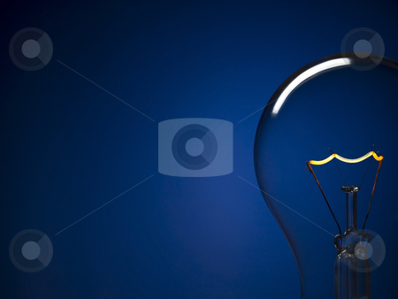 Bulb light over blue stock photo, Close up on a turned on light bulb over a blue background. Copy space. by Ignacio Gonzalez Prado