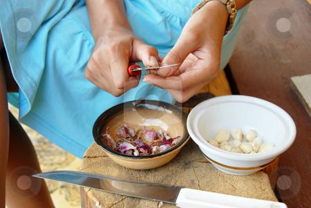 Peeling a garlic stock photo, Girl hands peeling a garlic with knife in yard outdoor by Julija Sapic