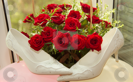 Wedding shoes stock photo, Beautiful wedding shoes on a background of a bouquet from red roses. by Sergey Goruppa